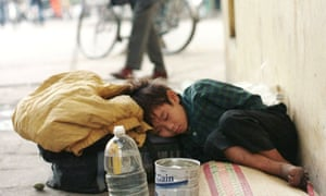 A young homeless child sleeps on the streets of Hanoi