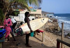 Khadjou Sambe, 25, Senegal's first female professional surfer, holds her surfboard as she watches the sea in Dakar.
