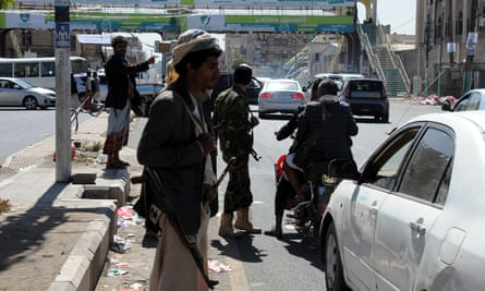 Houthi rebels check cars on a street leading to Sana'a airport
