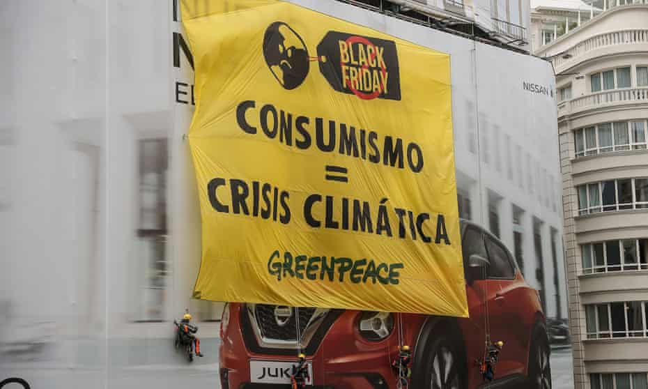 A banner denouncing consumerism is unfurled during a climate protest in Madrid