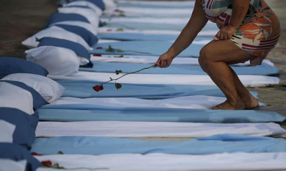 A woman lays a rose on mattresses symbolising coronavirus victims at a protest in Rio against Brazilian president Jair Bolsonaro's pandemic response