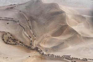 Tourists ride camels at the Mingsha mountain and crescent lake area in Dunhuang, China.