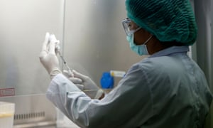 A researcher wearing a face mask and gloves in a laboratory