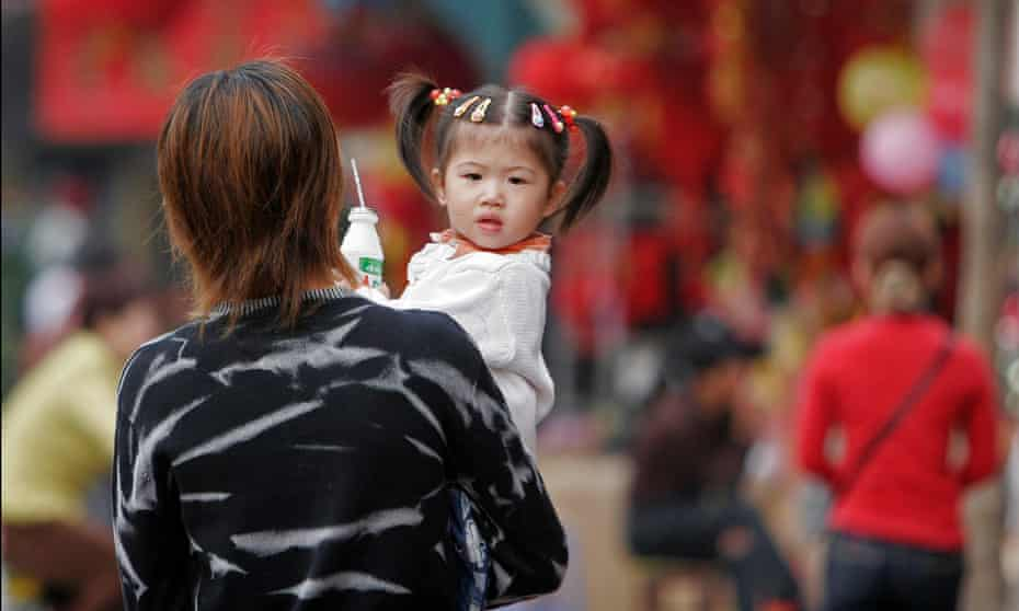 A toddler girl being carried in parent's arms, early morning in Shanghai.