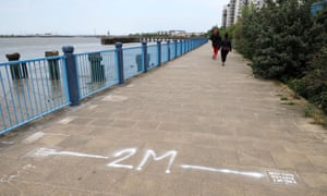 People exercising and maintaining physical distance on Thames Walk, Erith, Kent.