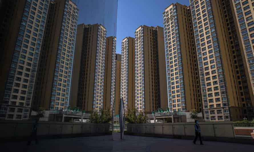 A woman walks through Evergrande city plaza, next to its apartment buildings in Beijing.