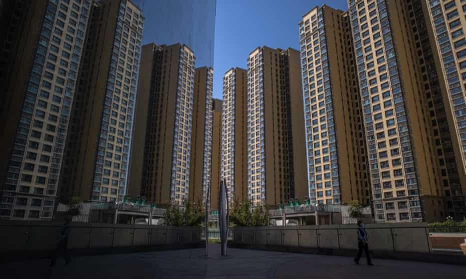 A woman walks in the town square of Evergrande, next to its apartment buildings in Beijing.