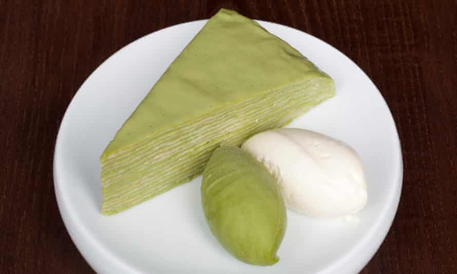green tea-flavoured crêpe cake, consisting of layers of thin pancake, next to two scoops of ice cream