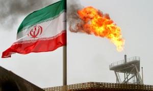 A gas flare on an oil production platform is seen alongside an Iranian flag
