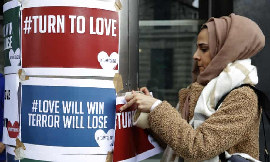 A woman puts up posters from the multi-faith group Turn to Love during a vigil at New Zealand House in London.