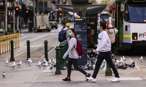People walk along Flinders Street in Melbourne on Sunday as Victoria reported 392 new locally acquired Covid cases.