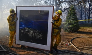 Firefighters remove a painting and Chirstmas tree from a house in Bel-Air on Wednesday.