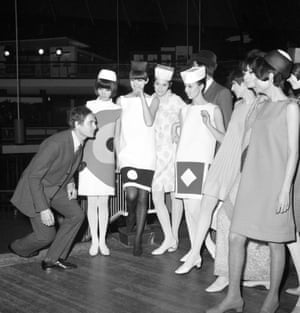 Cardin demonstrates a curtsey to models at a final rehearsal before showing his collection to Princess Margaret and Lord Snowdon at the Commonwealth Institute, London, 1966