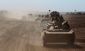 Iraqi military vehicles advance towards the village of Sheikh Younis, south of Mosul