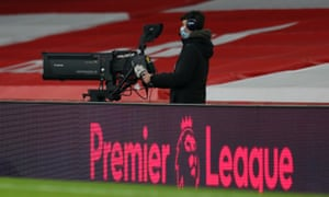 A television camera operator behind the Premier League logo