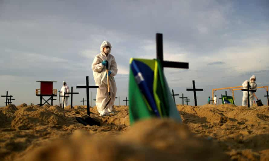 Activists wearing protective gear dig graves on Copacabana beach to symbolize those who died of coronavirus in Rio de Janeiro, Brazil, on 11 June.