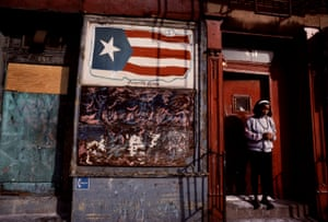 Girl on a doorstep next to an image of the Puerto Rican flag on a wall