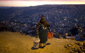 A woman walks with two buckets to wait for a water bowser to arrive near her neighbourhood in La Paz