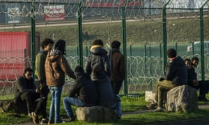 Migrants gather near a barbed-wire fence surrounding a lorry park in Calais.