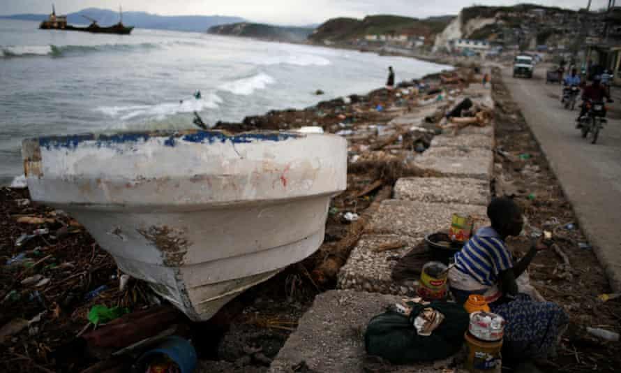 woman eats next to a boat after Hurricane Matthew hit Haiti
