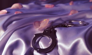 A pair of handcuffs and rose petals on a bed