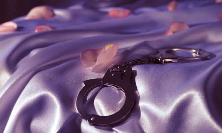 Close up image of handcuffs on a purple velvet background.