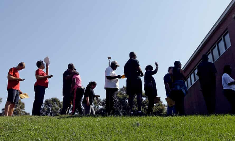 October. 20, 2016, people line up under the morning sun for early voting at a center in Raleigh, North Carolina.