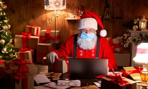 Santa wearing face mask holding Christmas gift on xmas eve using laptop