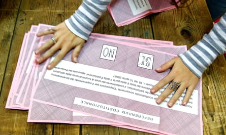 A volunteer counts ballots for a referendum on constitutional reform at a polling station in Rome, Italy.