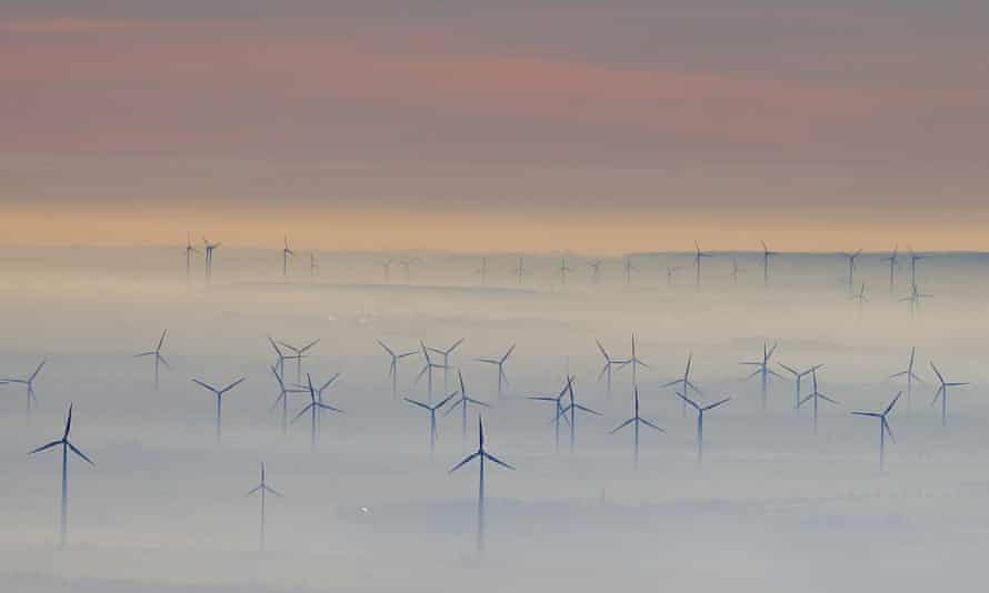 Wind turbines shrouded in fog near Petersberg mountain, Germany.
