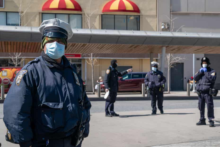 New York Police Department (NYPD) officers wear protective masks at the Fordham bus hub in the Bronx borough of New York, U.S., on Thursday, April 2, 2020. In four months, the new coronavirus infected more than 1 million people and killed more than 51,000. The U.S. accounts for a quarter of the cases.