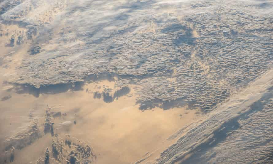 A photo taken from the International Space Station shows the sun reflected off snow and ice with clouds and shadows making a surreal landscape.