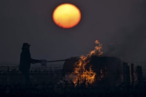 Touraine, France. A winegrower burns a bale of straw in the vineyards to protect them from frost, as the sun rises at the heart of the Vouvray vineyard
