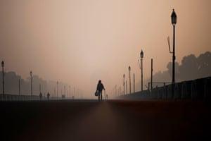 An elderly man walks along a street near India Gate in heavy smog conditions in New Delhi.