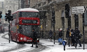 People walk in the street during a heavy snow in London.