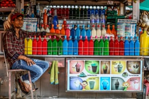 A street food vendor in Mumbai, India, waits for customers. His multicoloured rows of syrup are used to make gola – a drink made with shaved ice