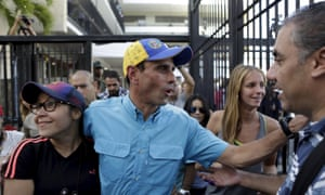 Venezuelan opposition leader Henrique Capriles greets supporters after casting his vote at a polling station in Caracas<br>