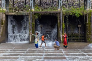 A family plays precariously in the spillway of Bidur's hydroelectric dam. The canal above the dam provides both electricity and water supply to this Nepali town.