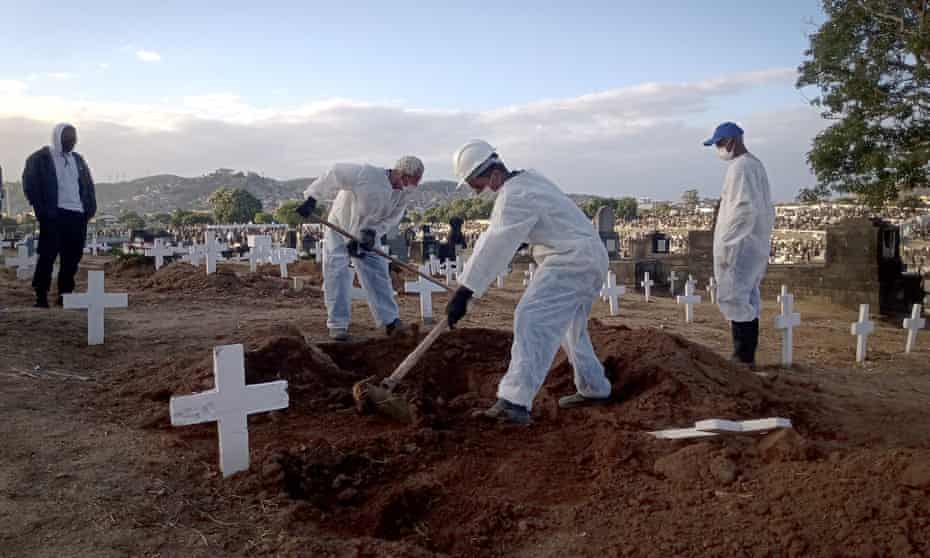 Funeral workers carry out burials of Covid victims at Inhaúma cemetery in Rio de Janeiro