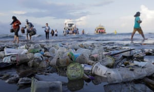 Tourists and local residents disembark a boat amid plastic rubbish in Sanur, Bali