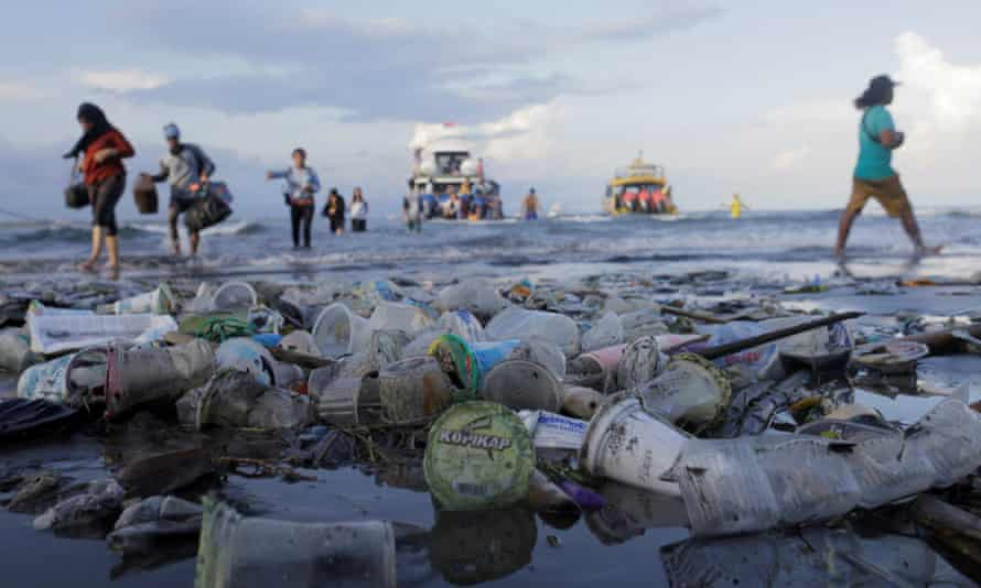Tourists and local residents disembark a boat coming from nearby Nusa Penida island as plastic trash pollutes the beach in Sanur, Denpasar, Bali, Indonesia April 10, 2018.