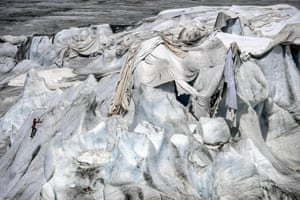 A woman ice-climbs next to insulating foams wrapping up the Rhône Glacier which has been shrinking under the summer sun near Gletsch, Switzerland. A second heat wave is forecast to hit the country in the next few days.
