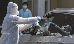 A doctor collects a coronavirus test from a car driver at a test centre on the grounds of a school in Fürstenwalde, Germany