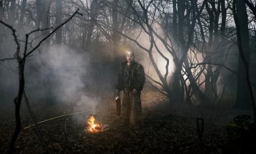 Steve Hart standing in woodland next to a campfire, holding a dead rabbit by its feet