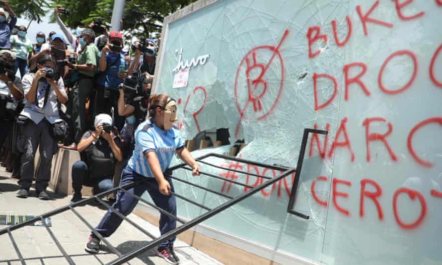 A demonstrator vandalises a Chivo Wallet bitcoin ATM during a protest against President Nayib Bukele's policies on Independence Day in San Salvador, 15 September.