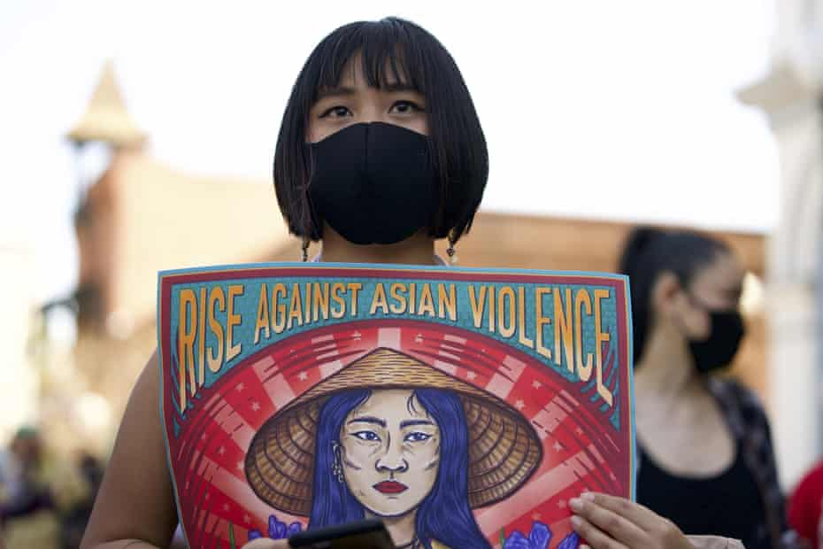 Ally Vega holds a poster by artist Pauline Cuevas, as she joins a rally against Asian hate crimes in Los Angeles last month.