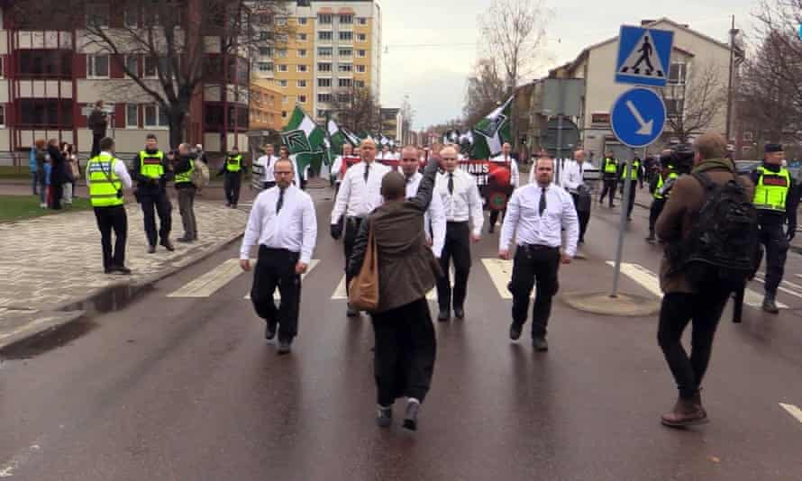 Tess Asplund tries to block Nordic Resistance Movement members as they march through the town of Borlänge, Sweden, on a 1 May rally in 2016.