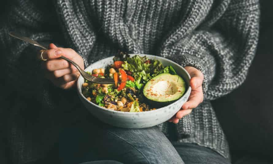 Woman eating fresh salad, avocado, beans and vegetables