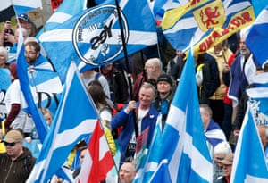 People wave Saltire flags as they attend the All Under One Banner march through Glasgow, Scotland. Thousands of campaigners for Scottish independence are holding marches through Glasgow