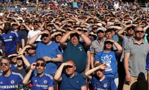 Chelsea fans shield their eyes from the sun during the game.